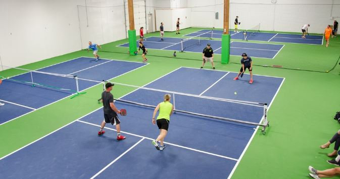 This is an image of indoor pickleball courts with people playing on each court.